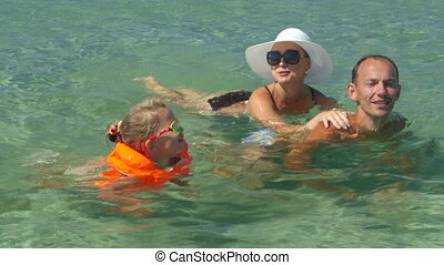 Happy family on summer vacation have fun swimming together with little daughter