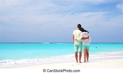 Happy family on the beach. Young lovers enjoy their honeymoon. SLOW MOTION VIDEO.