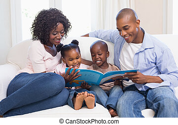 Happy family on the couch reading storybook at home in the...