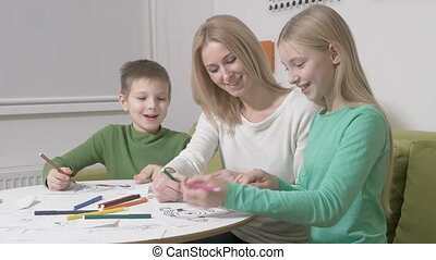 Happy family or Mother with cute children drawing with colorful pencils