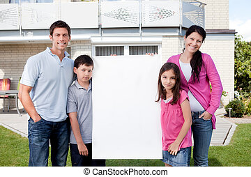 Happy family outside with a blank sign board