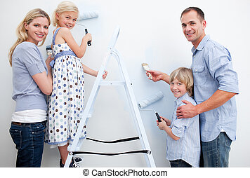 Happy family painting a room with brushes