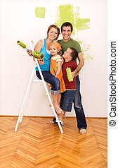 Happy family painting their new home together - Happy family...