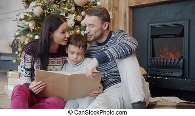 Happy family parents and kid reading book and talking on Christmas day at home
