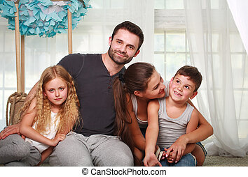 Happy family parents and two children at home