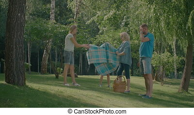 Happy three generation family placing picnic blanket in the park on a sunny day. Multi generation arranging place for picnic in forest on summer weekend. Slow motion.
