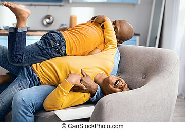 Happy family playfully tussling on the sofa