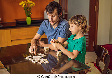 Happy Family Playing Board Game At Home.