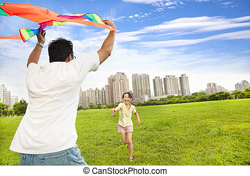 happy family playing colorful kite in the city park
