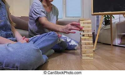 Happy family playing  game with wooden blocks at home