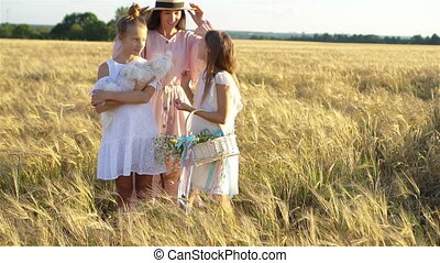 Happy family in a wheat field. Mother and her little daughters on summer meadow