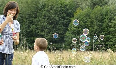 Happy family playing in nature. Mom and children are blowing bubbles. A girl and a boy are playing with her mother. Camping with the family. Glade near the forest. The sun is shining and it's raining.