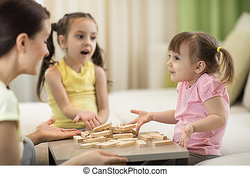 Happy family playing jenga together at home. Mother and daughters having fun in living room.