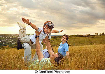 Happy family playing on grass in nature at sunset
