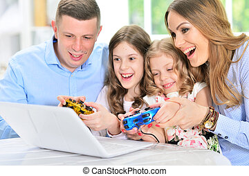 Family playing on laptop at table
