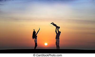 happy family playing on the beach at sunset