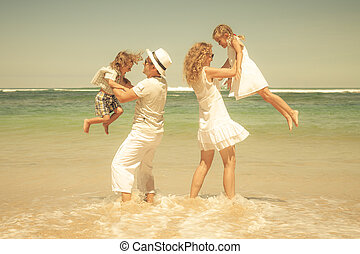 Happy family playing on the beach at the day time