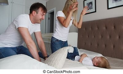 Happy family playing to pillows fight on bed at home