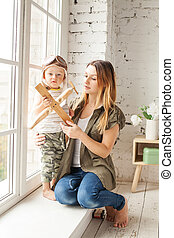 Happy Family Playing Together at Home. Pretty Mom and her Son with Plane Toys