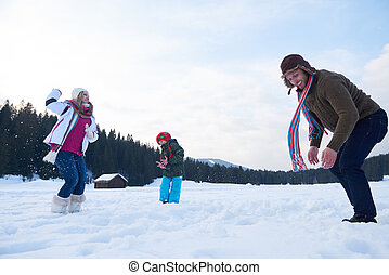 happy family playing together in snow at winter