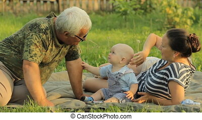 Happy family playing with a little toddler boy in an summer park with beautiful grass. Mother, baby, grandfather