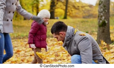 happy family playing with autumn leaves at park - family,...