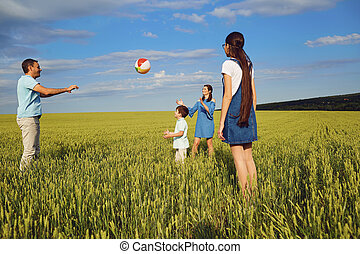 Happy family playing with ball in summer field