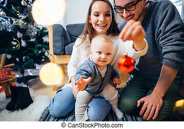 Happy family playing with Christmas balls at home