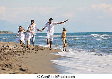 happy family playing with dog on beach - happy young family ...