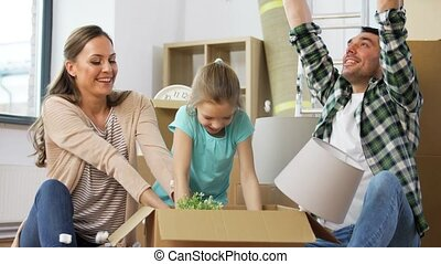 happy family playing with foam peanuts at new home - ...