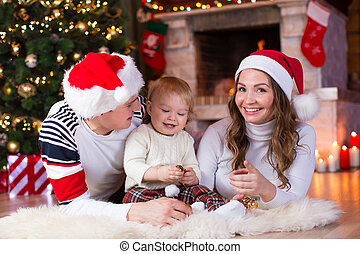 Happy family playing with little son lying near Christmas tree and fireplace