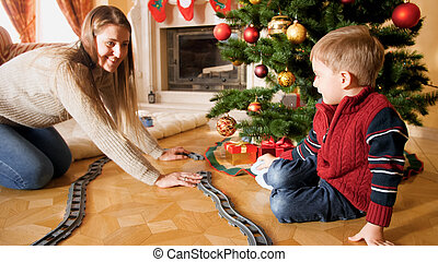 Happy family playing with toy railroad on Christmas morning. Child receiving presents and toy on New Year or Xmas