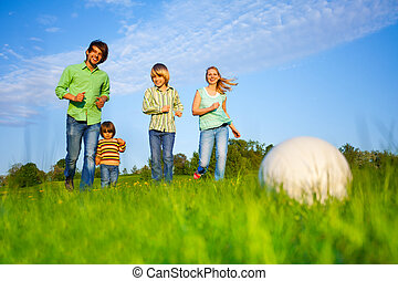 Happy family plays football in summer