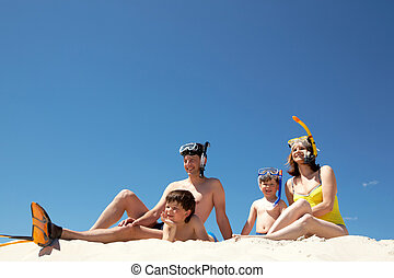 Portrait of modern family sitting on sandy beach against blue sky