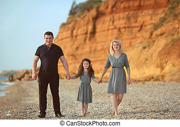 Happy family portrait on the beach. Father and mother walking with their daughter.