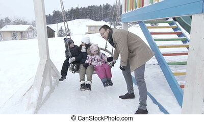 Happy family portrait on wooden swing out in the winter, slowmotion