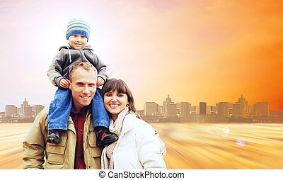 Happy family portrait outdoors smiling on the road in city