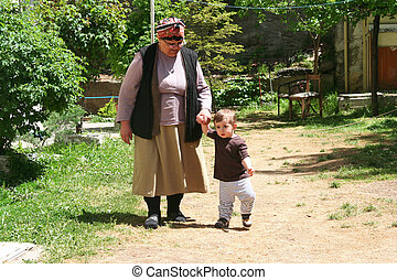 happy family portrait - grandmother teaching walking to her...