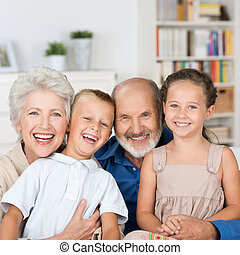 Happy family portrait with a loving elderly couple hugging...
