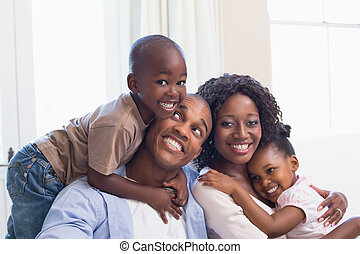 Happy family posing on the couch together at home in the ...