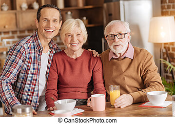 Happy family posing while having breakfast in the kitchen