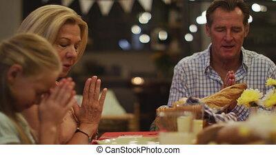 Happy family praying before dinner