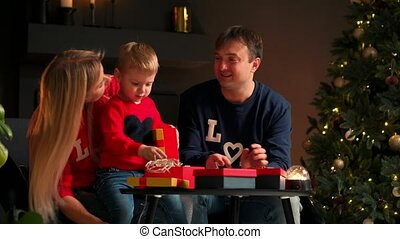 Happy family preparing for Christmas celebration: mother, father and kid smiling and talking while open gifts at home sitting on the couch in the Christmas interior. Warm and cozy home atmosphere