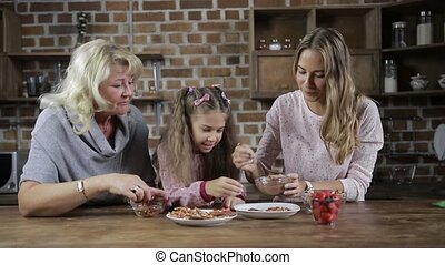 Happy family preparing homemade cookies in kitchen -...