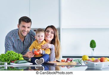 Happy family preparing vegetables together at home in the kitchen
