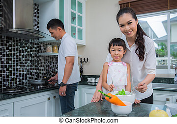 Happy family preparing vegetables together at home