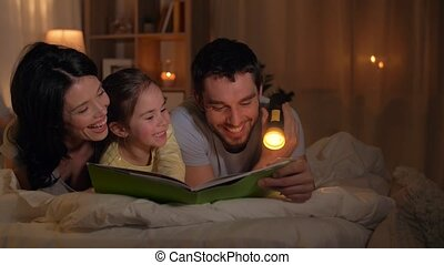 happy family reading book in bed at home - people and family...