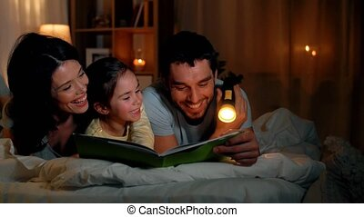 happy family reading book in bed at night at home - people...