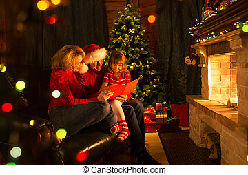 Happy family reading Christmas book sitting on sofa in front of fireplace in cozy living room in winter