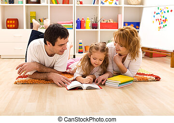 Happy family reading in the kids room - Happy family laying ...